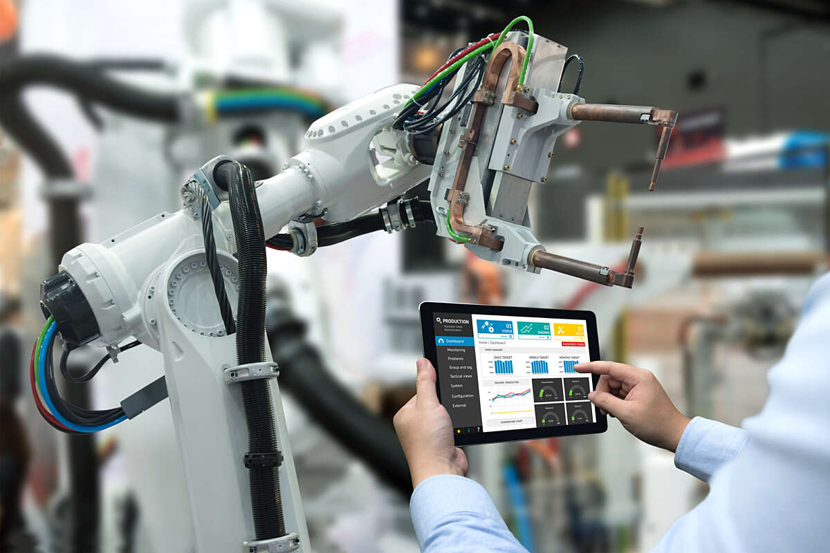 Engineer hand using tablet heavy automation robot arm machine in smart factory industrial with tablet real time monitoring system application original1