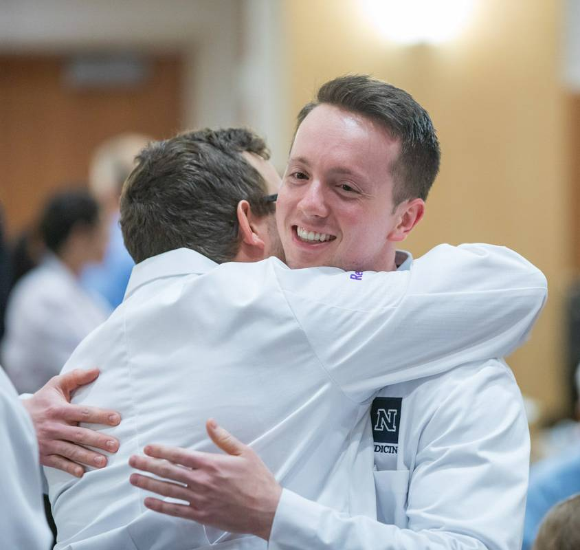 Students hugging at white coat ceremony