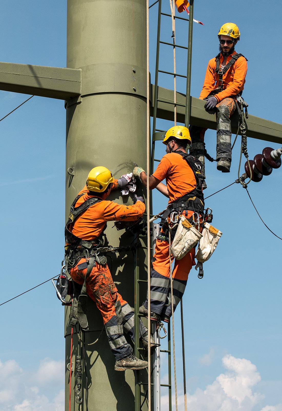 Drei Männer arbeiten an einem Elektro Mast