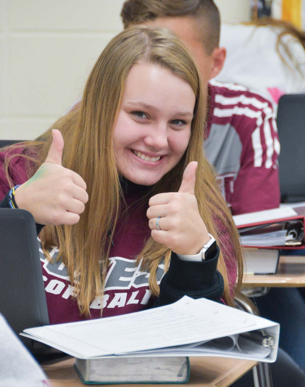 Smiling girl in class giving two thumbs up
