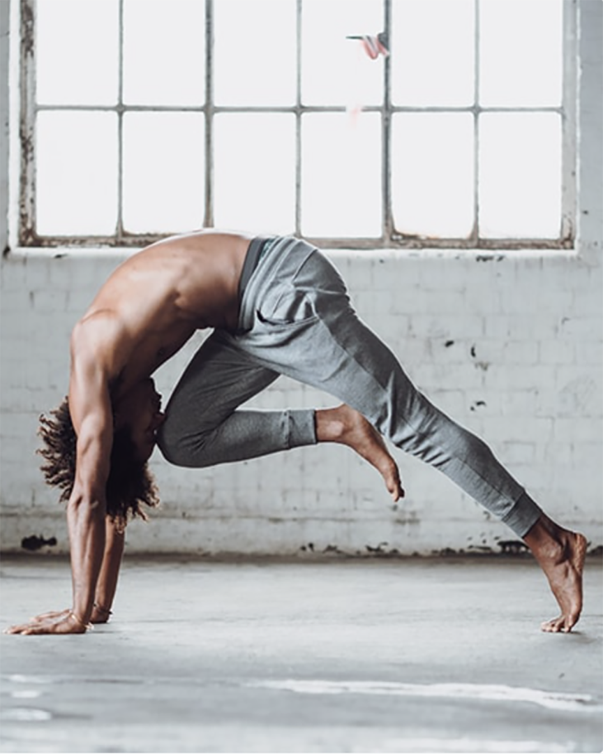 Warrior Addict eco-warrior sweat pants in grey in action modelled by Marc Laws yoga