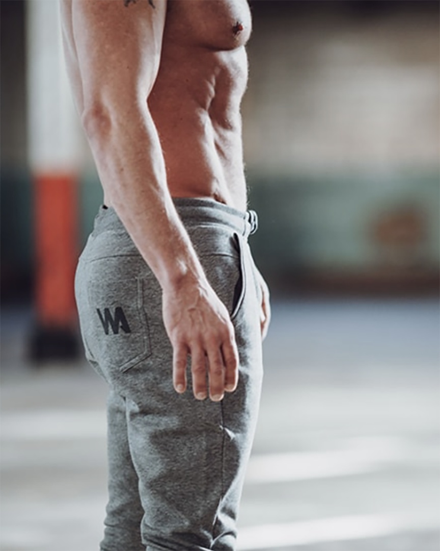Warrior Addict eco-warrior sweat pants in grey in action modelled by Caleb Jude Packham yoga