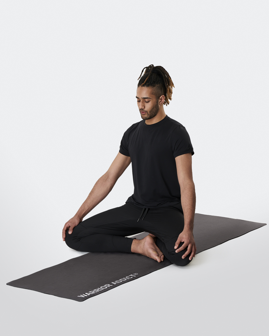 warrior addict the warrior light yoga mat in black micro fibre model is meditating